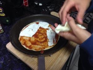 Forre a massa já pronta com molho de tomate e queijo